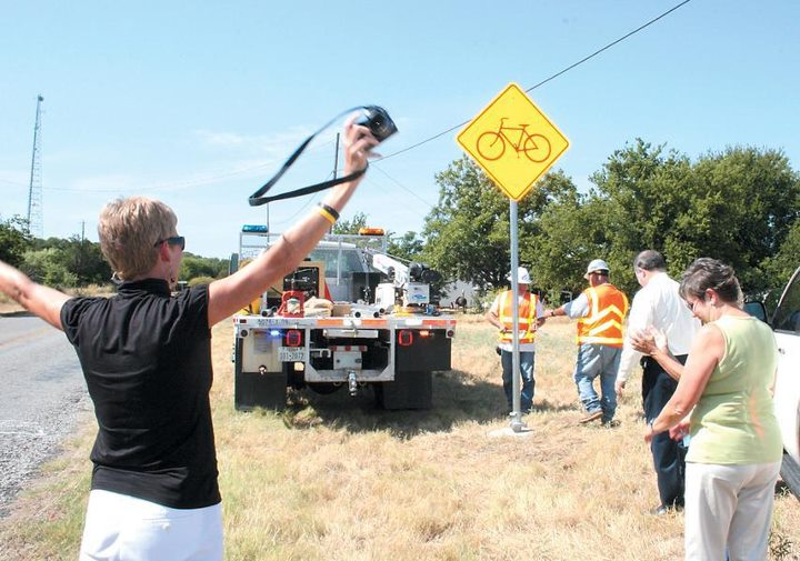Iris Stagner (left) celebrates the bicycle sign installation in Palo Pinto.