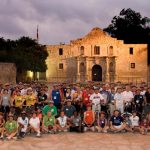 about 100 riders posed in front of the Alamo during a Mission Tour ride