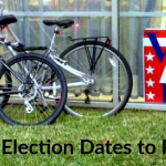 """two bicycles sit next to a """"Vote Here"""" sign"""