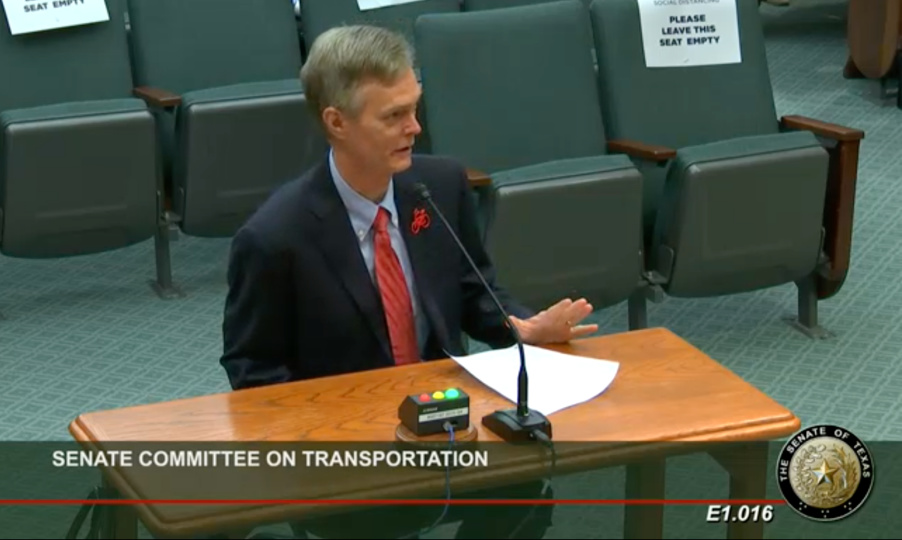 BikeTexas Executive Director Robin Stallings sits at the witness table in a Texas Senate Committee room facing the Transportation Committee (not pictured). He is speaking into the microphone.
