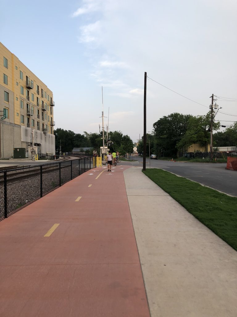 A two-way, separated bike path alongside a sidewalk. On the left is a railway track; on the right is the roadway.