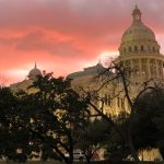 Texas Capitol at sunset. Dark trees sit in front of the building and pink clouds fill the sky behind it.   texas legislature, bicycle advocacy, biketexas